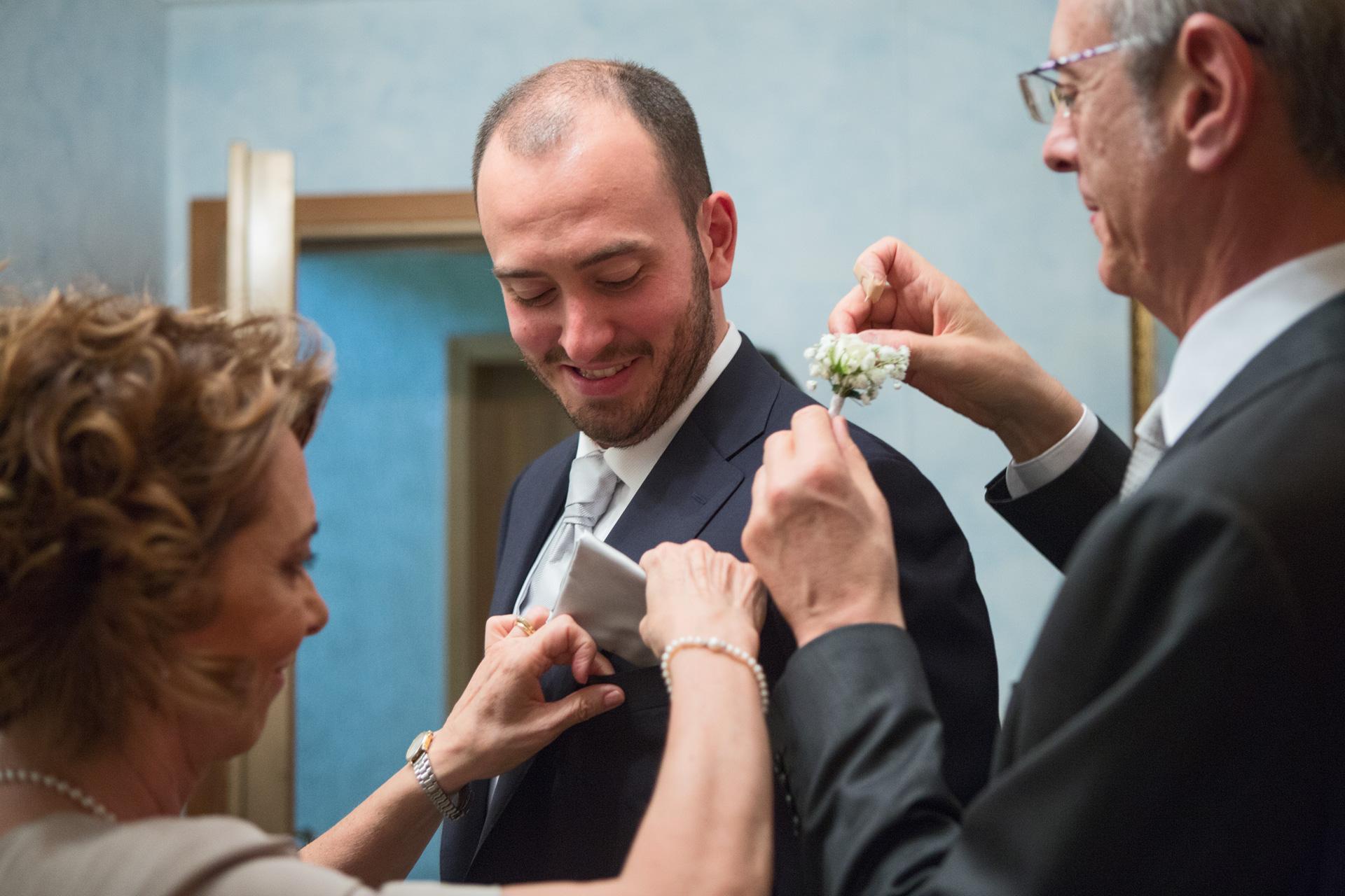 la mamma e il papà dello sposo lo aiutano con fiore all'occhiello e fazzoletto