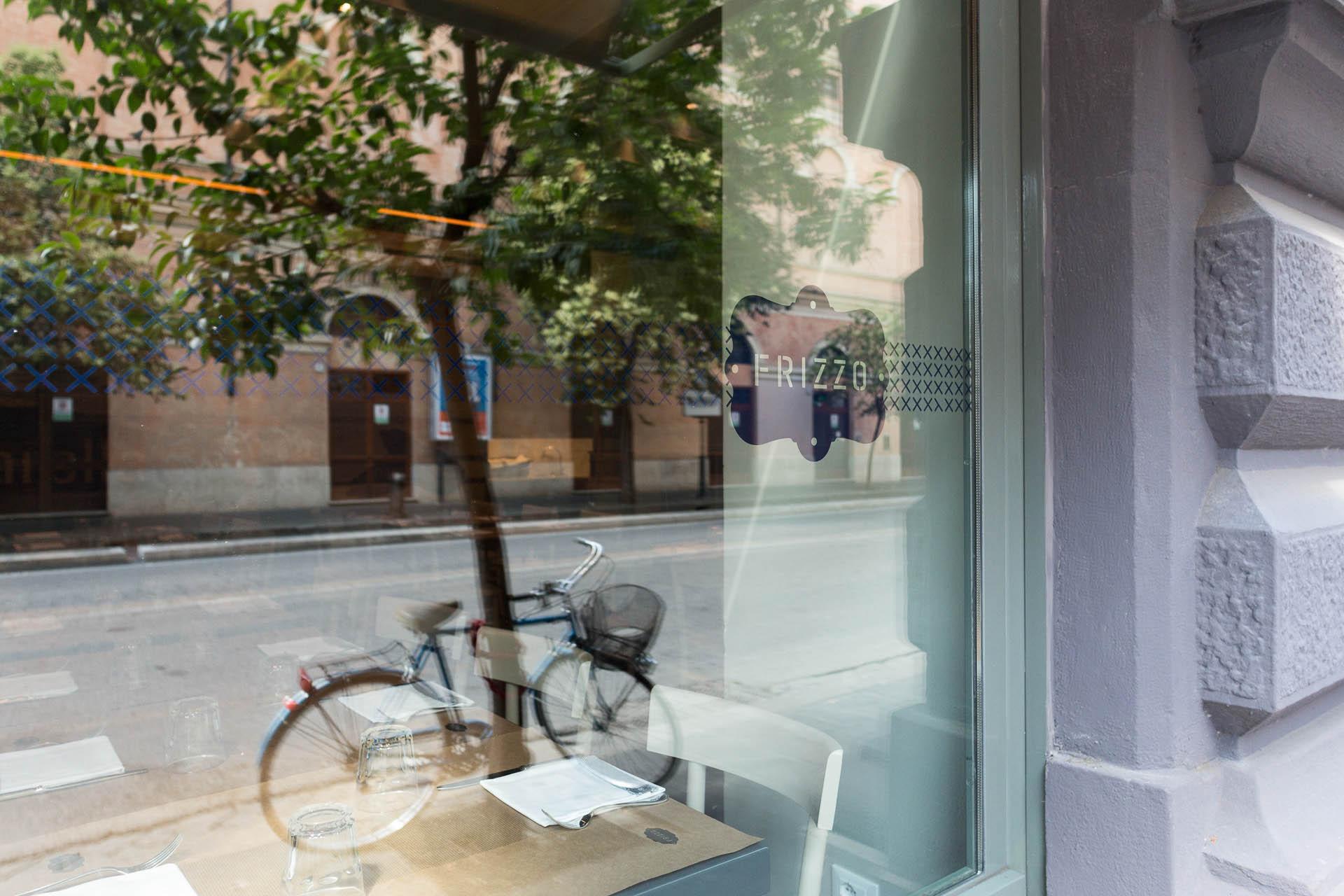 Fotografia d'interni: bicicletta riflessa nella vetrina di Frizzo, ristorante a Roma