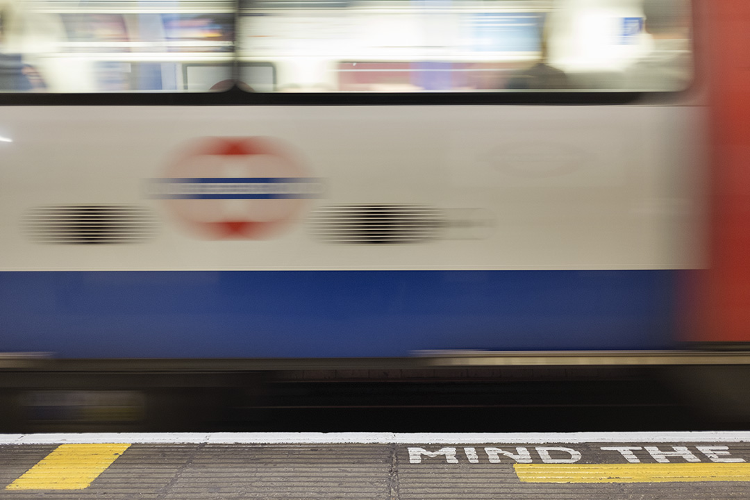 London underground train moves in front of mind the gap signal