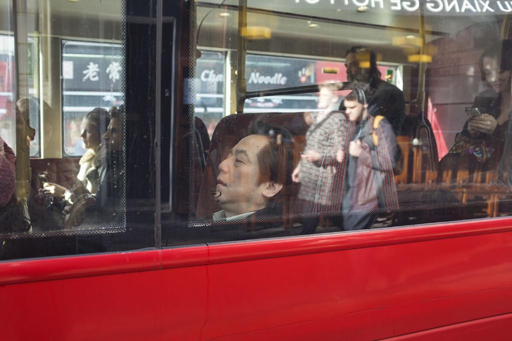 eastern man sleeping on a red double-decker bus in London