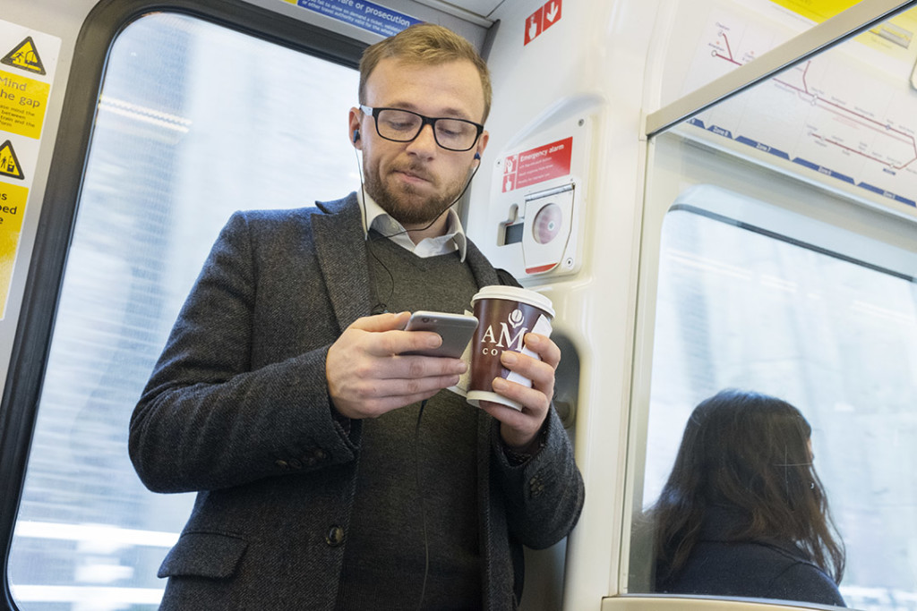 young man with a cup of coffee in the hand looks at his smartphone
